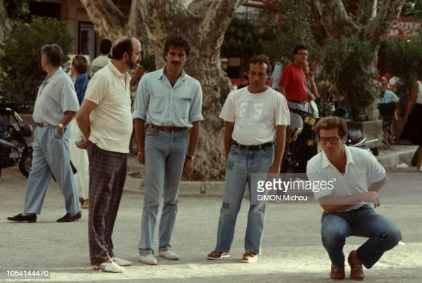Saint-Tropez, France - Août 1985 - Le chanteur Eddy MITCHELL en vacances avec son épouse Muriel et leur fille Pamela. Ici, jouant à la pétanque, sur...