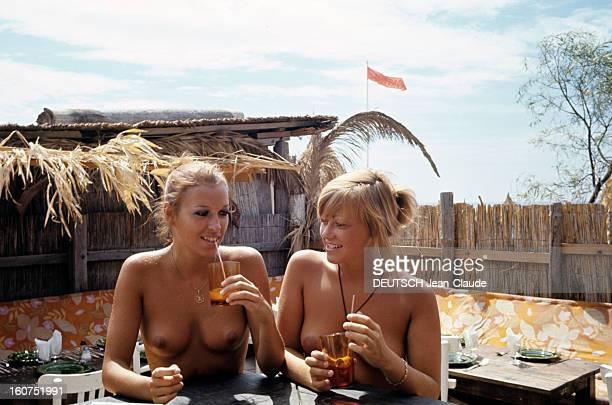 Sainttropez The Topless Peninsula SaintTropez août 1970 Au comptoir du bar de la plage de la Voile Rouge à Pampelonne deux femmes aux seins nus buvant