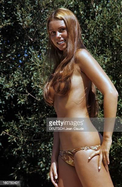 Sainttropez The Topless Peninsula SaintTropez août 1970 Portrait en extérieur de Béatrice BARCLAY souriante posant les seins nus dissimulés sous ses...
