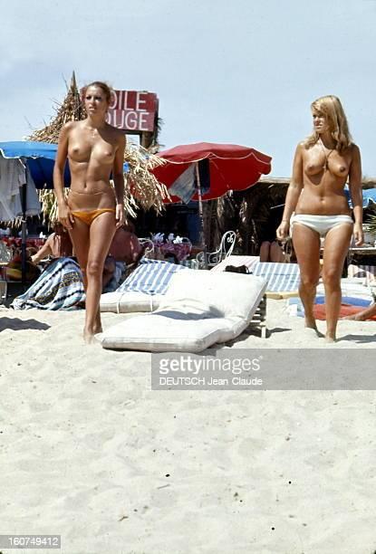 Sainttropez The Topless Peninsula SaintTropez août 1970 Sur la plage de la Voile Rouge à Pampelonne deux femmes aux seins nus marchant entre des...