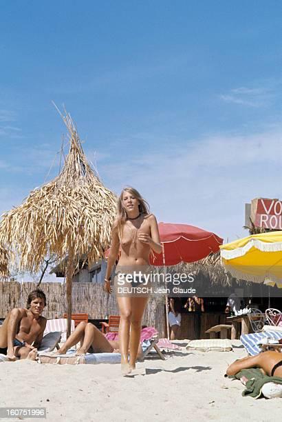 Sainttropez The Topless Peninsula SaintTropez août 1970 Sur la plage de la Voile Rouge à Pampelonne Hecate GOULD les seins nus marchant devant des...