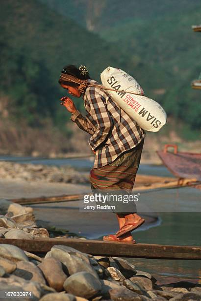 A woman totes a 50kilo sack of Siam Cement from a strap on her head unloading goods from a cargo boat for a new school in her tiny village along the...