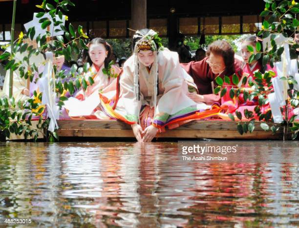 Saiodai unmarried woman who acts as the shrine maiden during the Aoi festival puts her hands to Mitarashi River to purify ahead of Aoi Festival on...