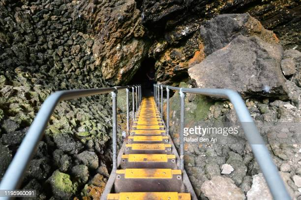 sair case leading into underground cave. - rafael ben ari stock-fotos und bilder