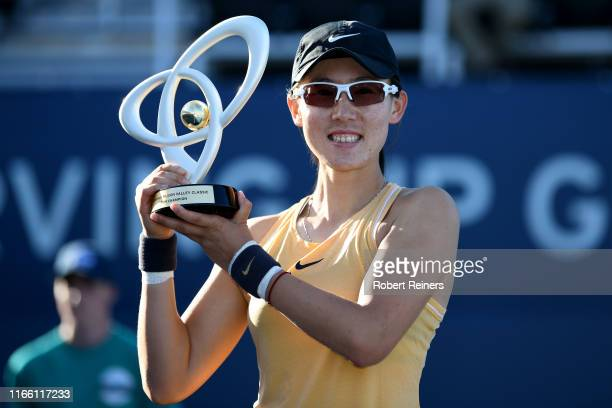 Saisai Zheng of China celebrates with the winner's trophy after defeating Aryna Sabalenka of Belarus in the singles final of the Mubadala Silicon...