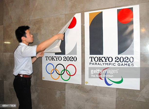 A Saitama prefecture government staff removes a poster of the 2020 Tokyo Olympics emblem at the headquarters after the Organising Committee...