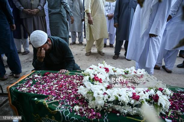 Sajid Shah the elder brother of plane crash victim Danish Shah mourns over the coffin of his brother during the funeral in Rawalpindi on May 25 2020...