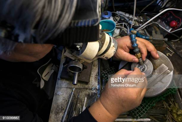 Sakamoto Metal President Kunio Sakamoto makes final touches to a metal mold for a bitcoin medal at the company's workshop on January 25 2018 in Tokyo...