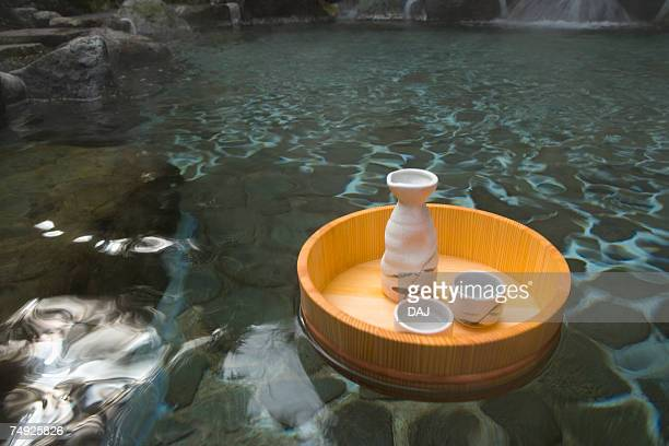 Sake bottle and cups in a wooden tub floating on a Japanese public bath, hot spring, high angle view, Japan
