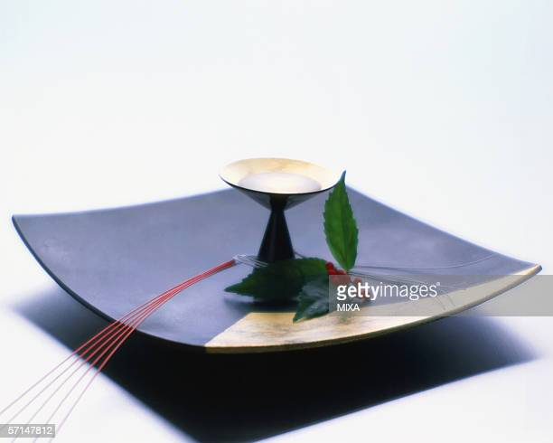 Sake cup and nandina on plate