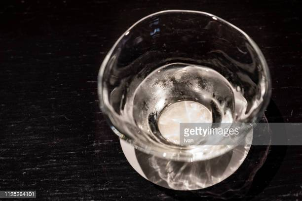 sake in glasses cup with black background - saki stock photos and pictures
