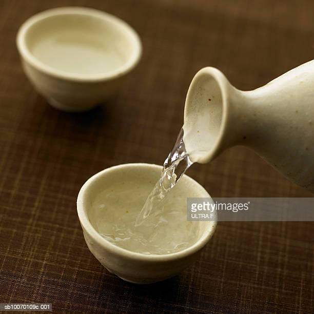 Sake is poured into sake cup, studio shot
