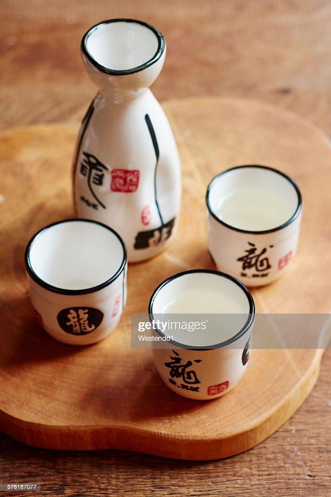 Sake set with 4 cups and a carafe, two cups filled with sake : Stock Photo
