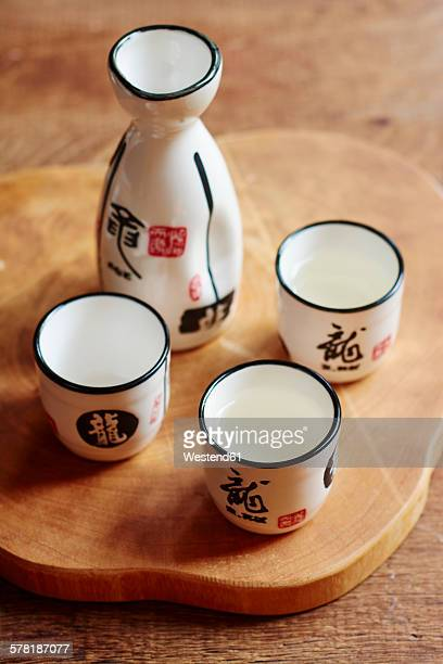 Sake set with 4 cups and a carafe, two cups filled with sake