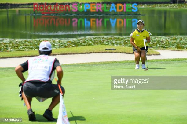 Saki Asai of Japan and her caddie line up a putt on the 9th green during the final round of Rakuten Super Ladies at Tokyu Grand Oak Golf Club on July...