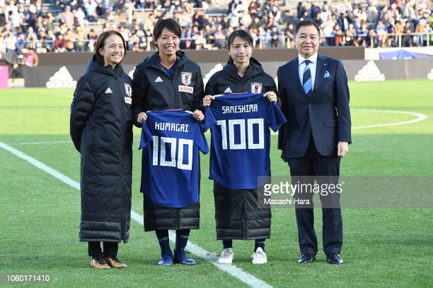 Saki Kumagai and Aya Sameshima of Japan pose for photographs with a shirt to mark their 100th appearance for the national team along with head coach...