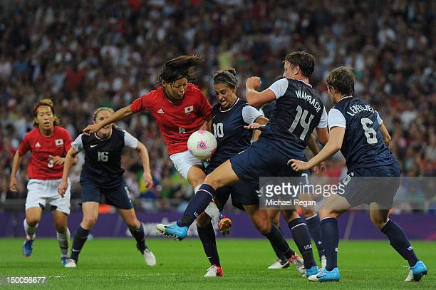Saki Kumagai of Japan attempts a shot against Carli Lloyd Abby Wambach and Amy LePeilbet of the United States during the Women's Football gold medal...