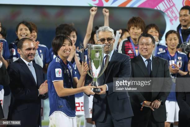 Saki Kumagai of Japan lifts the trophy after winning the AFC Women's Asian Cup final between Japan and Australia at the Amman International Stadium...