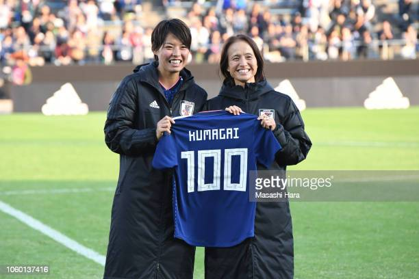 Saki Kumagai of Japan poses for photographs with a shirt to mark her 100th appearance for the national team along with head coach Asako Takakura...