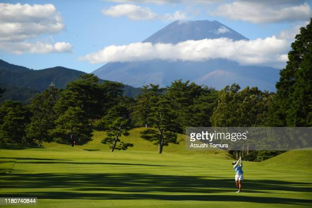 Saki Takeo of Japan hits her second shot on the 14th hole as Mt. Fuji is seen on the background during the final round of the Stanley Ladies at Tomei...