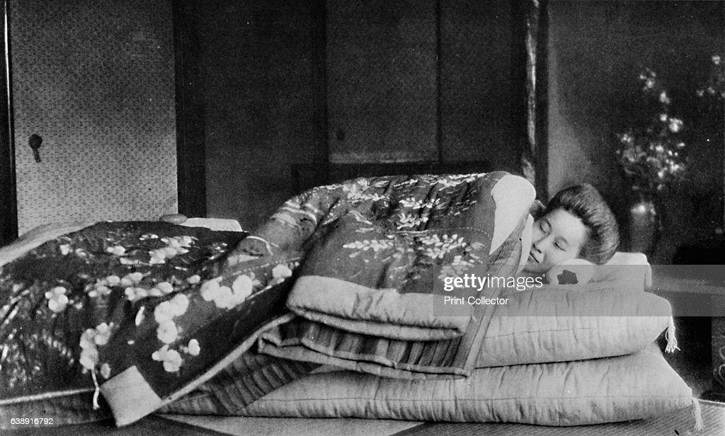 'Saki, the housekeeper sleeps on a mattress with hard pillow under a quilted kimono', c1900, (1921) : ニュース写真