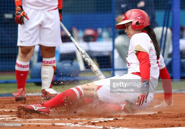 Saki Yamazaki of Team Japan slides into home plate to score on a passed ball in the first inning against Team United States during softball opening...