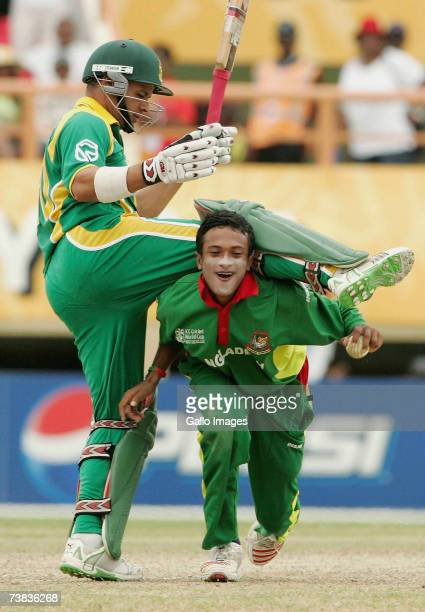 Sakib Al Hasan of Bangladesh tangles with runner Ashwell Prince of South Africa as he dismisses Justin Kemp of South Africa caught and bowled during...