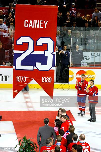 Saku Koivu and Guy Carbonneau look on from the side as Bob Gainey along with his family watches as his jersey number 23 retired by the Montreal...