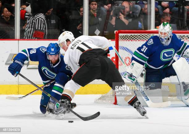 Saku Koivu of the Anaheim Ducks and Ryan Stanton of the Vancouver Canucks battle for the puck in front of Eddie Lack of the Canucks during their NHL...