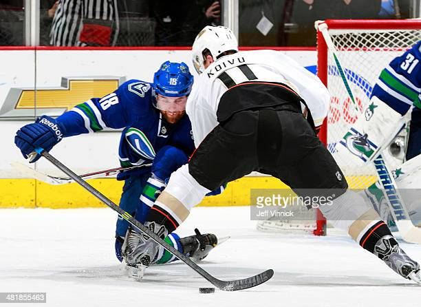 Saku Koivu of the Anaheim Ducks checks Ryan Stanton of the Vancouver Canucks during their NHL game at Rogers Arena March 29 2014 in Vancouver British...