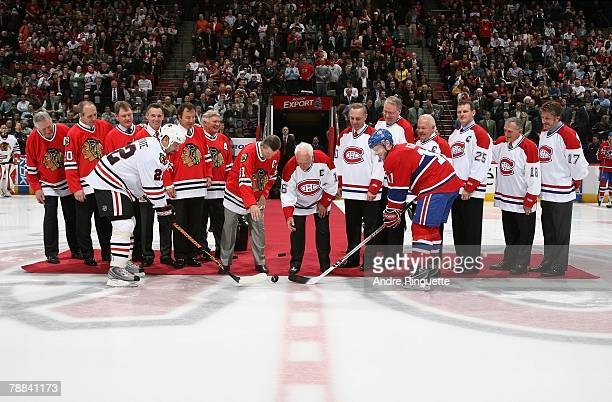 Saku Koivu of the Montreal Canadiens and Martin Lapointe of the Chicago Blackhawks take a ceremonial faceoff from Stan Mikita and Henri Richard on a...