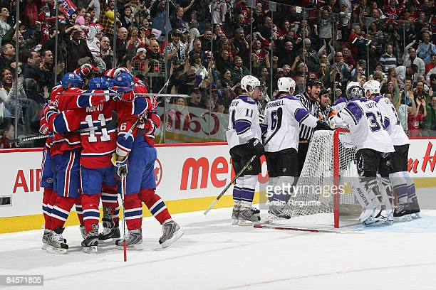 Saku Koivu of the Montreal Canadiens celebrates the game winning goal with teammates as members of the Los Angeles Kings discuss the play with...