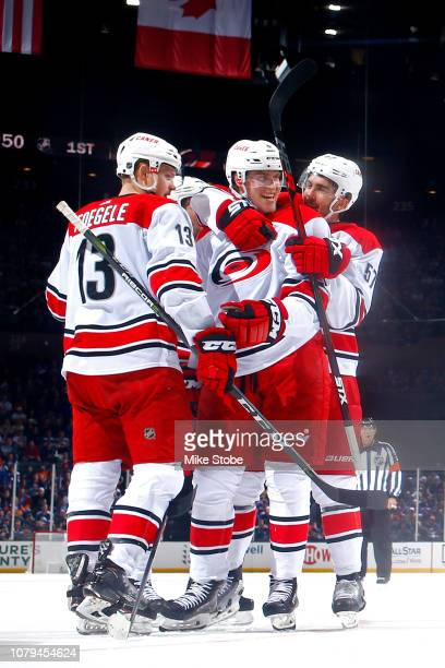 Saku Maenalanen of the Carolina Hurricanes is congratulated by his teammates after scoring his first NHL goal during the first period against the New...