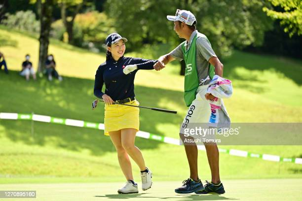 Sakura Koiwai of Japan elbow bumps with her caddie after winning the tournament on the 18th green during the final round of the GOLF5 Ladies...