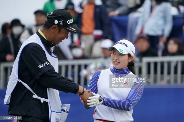 Sakura Koiwai of Japan shakes hands with her caddie on the 18th green during the final round of the TOTO Japan Classic at Seta Golf Course on...