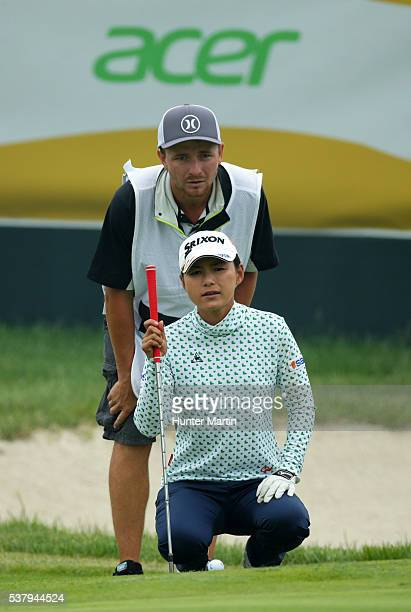 Sakura Yokomine of Japan and her caddie line up her putt on the 18th hole during the first round of the ShopRite LPGA Classic presented by Acer on...