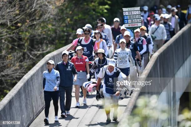Sakura Yokomine of Japan and Minami Katsu of Japan walk on the bridge during the final round of the CyberAgent Ladies Golf Tournament at the Grand...