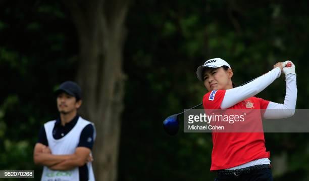Sakura Yokomine of Japan hits a drive as her husband and caddie Morikawa Yotaro looks on during the third and final round of the ShopRite LPGA...