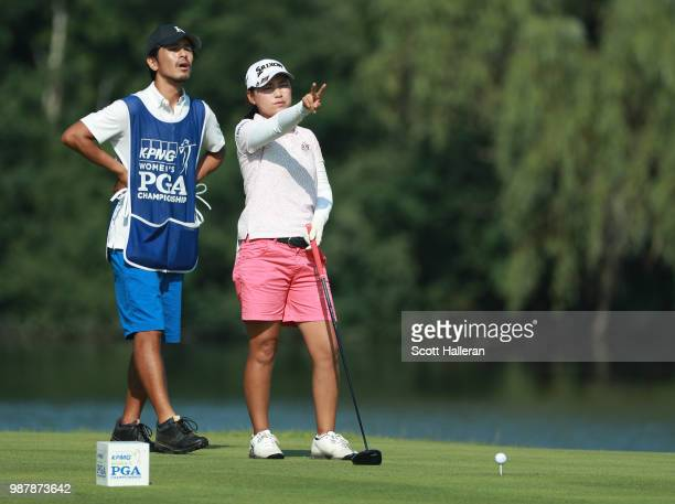 Sakura Yokomine of Japan lines up her tee shot with her caddie on the seventh hole during the third round of the KPMG Women's PGA Championship at...