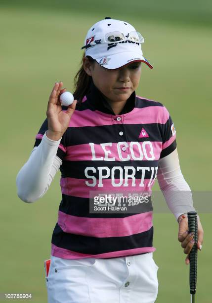 Sakura Yokomine of Japan waves to the gallery on the 18th green during the completion of the second round of the 2010 US Women's Open at Oakmont...