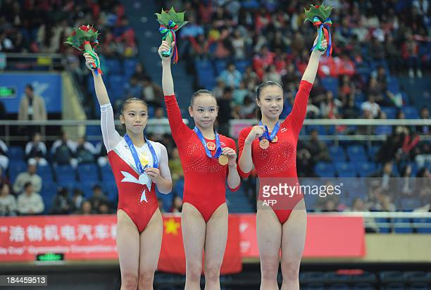 Sakura Yumoto of Japan Tan Sixin of China and Jiang Tong of China wave to the audience on the awards ceremony of women's floor exercises gymnastics...