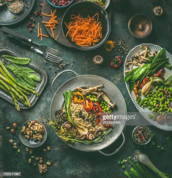 salad buddha bowl with grilled vegetables, edamame soybeans and mushrooms on dark rustic background with ingredients and cutlery. - コース料理 ストックフォトと画像