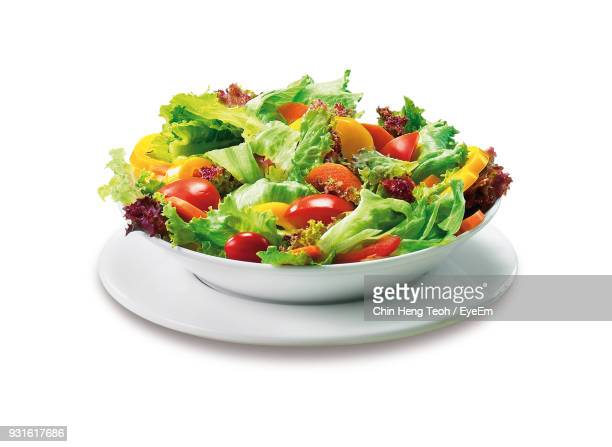 salad in bowl on plate against white background - lettuce stock pictures, royalty-free photos & images