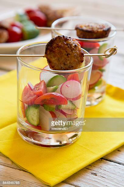 Salad in glass and meatball on skewer