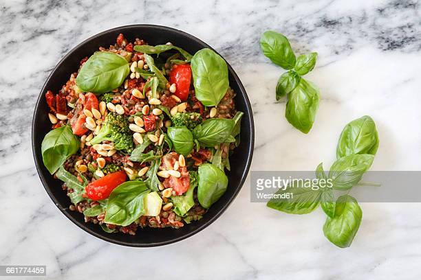 Salad made of rice, lentils, different vegetables and roasted pine nuts