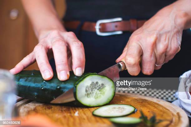 salad preparation: slicing cucumber 2 - pepino fotografías e imágenes de stock