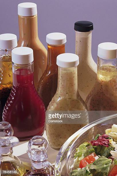 salad with assorted bottles of dressing - salad dressing stock pictures, royalty-free photos & images