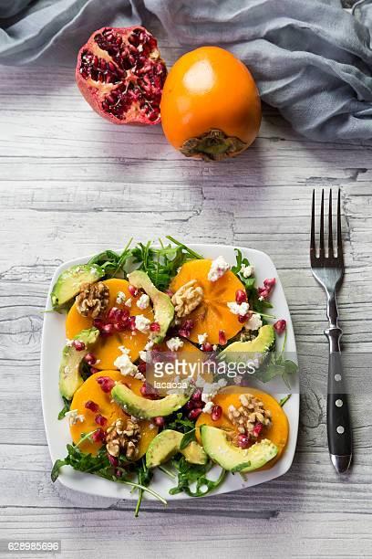 salad with avocado, rocket, kaki, pomegranate seed, feta, walnuts