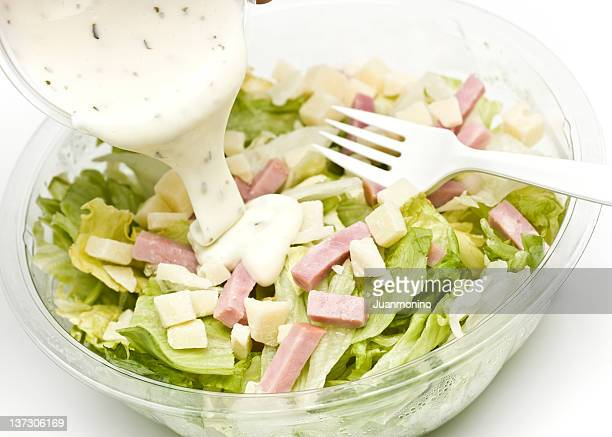 salad with bits of ham and dressing being poured over