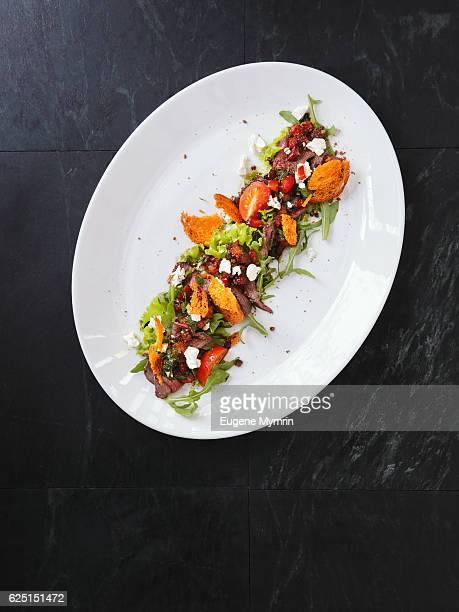 Salad with deer, arugula and vegetables
